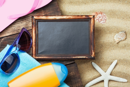 blackboard and beach gear lie on the sand with shells Stock Photo - 20343514