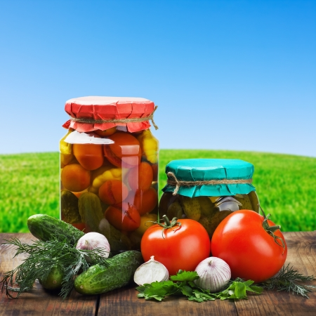canned and fresh vegetables on background of blue sky Stock Photo