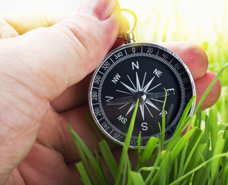 compass in hand on a background of green grass Stock Photo - 20343522