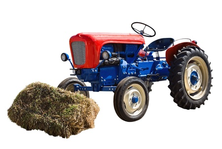 old tractor and a shock of hay isolated on a white background