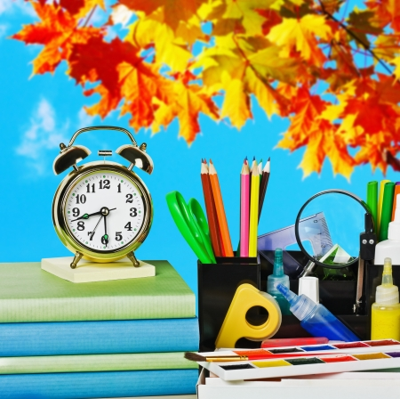 alarm clocks and school supplies on the background of autumn leaves photo