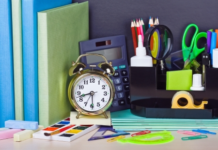 alarm clocks and school supplies on the school desk photo