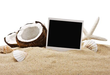 chopped coconut and photoframe on the sand in isolation photo