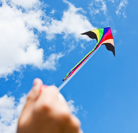 windy energy: kite flying in a beautiful sky clouds. Focus on the kite. Stock Photo
