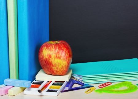 ripe apple and school supplies on the desk photo