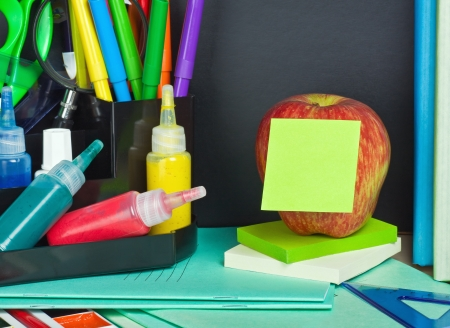 paper sticker pasted on the apple on the background of school supplies photo