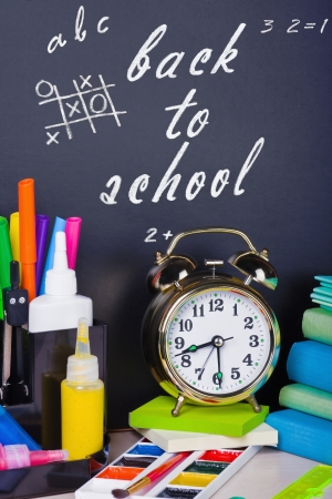 alarm clocks and school supplies on the background photo