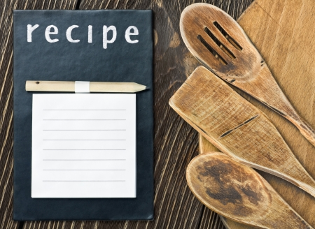Wooden kitchen utensils and a notepad to write a recipe photo