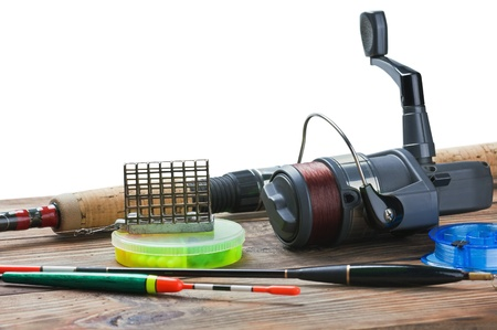 fishing tackle on a wooden table isolated on a white background photo
