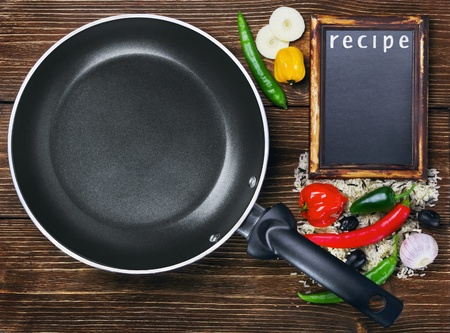rice with vegetables next to a frying pan and a blackboard for the recipe photo