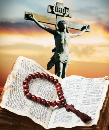 wooden rosary on the Bible against the crucifixion of Christ photo