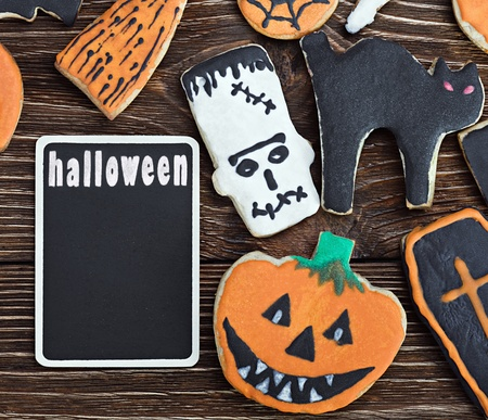 Handmade Halloween cookies on a wooden background and a blackboard photo