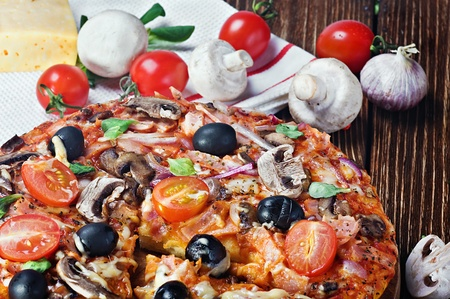 pizza with mushrooms and cheese on a wooden table photo