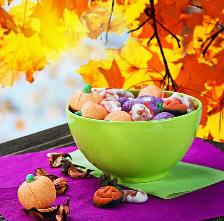 sweets and candies for the holiday halloween on a batskground autumn leaves photo