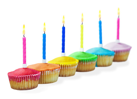 Birthday cupcakes in different colors isolated on white background photo