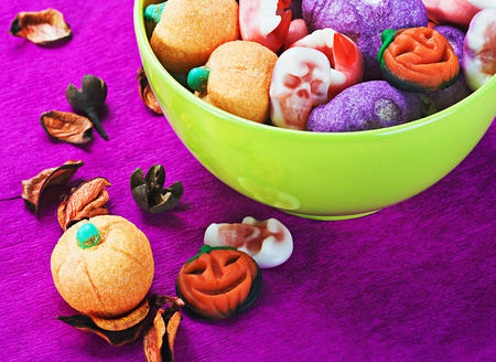 sweets and candies for the holiday Halloween. Focus on the pumpkin in the foreground photo