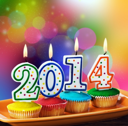 burning candles with the symbol of the new year on the cupcake   Stock Photo