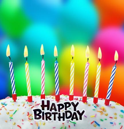 brennende Kerzen auf einem Geburtstagskuchen auf dem Hintergrund von Ballons Standard-Bild