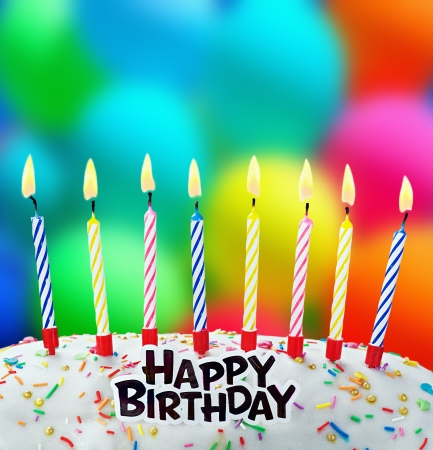 tortas cumpleaÑos: quema de velas en una torta de cumpleaños en el fondo de los globos Foto de archivo
