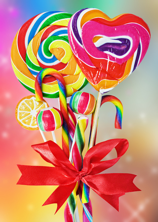 colored sweets with red ribbon bow on a colored background photo