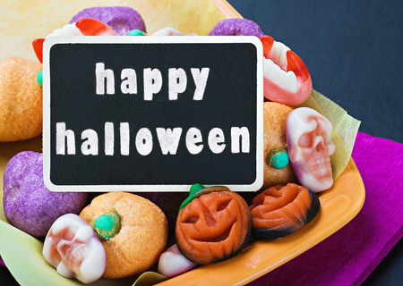sweets and candies for Halloween and blackboard with congratulations photo