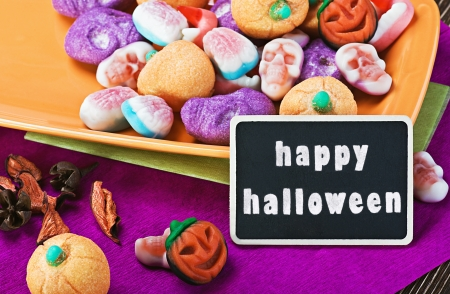 Halloween candy and blackboard for writing greetings photo