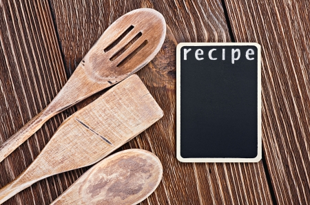 Wooden kitchen utensils and a blackboard to write a recipe photo