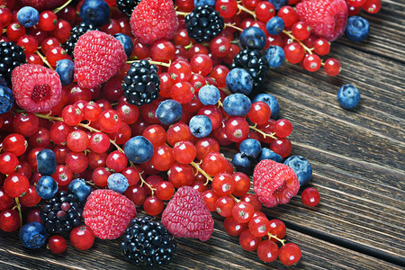 Fresh blackberries, currants, raspberries, blueberries on a wooden table photo