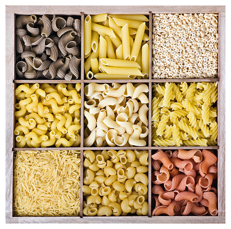Assortment of Italian pasta in a wooden box on a white background photo