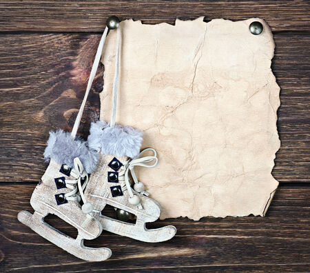 Christmas wooden toy figure skates and a piece of old paper for text photo