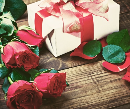 red roses and holiday gift on a wooden table. artistic toning photo