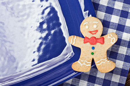 smiling gingerbread man on a blue plate photo