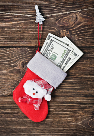 Christmas sock with gift dollars on a wooden background photo