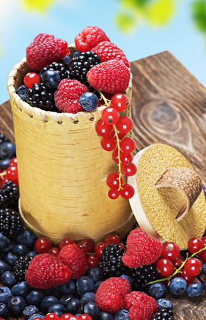 Assorted Fresh berries on a wooden table photo