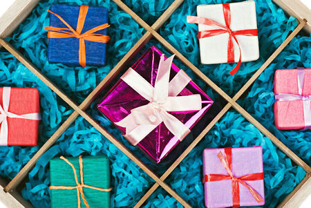 wooden box with gifts in colorful packaging. Focus on the central gift photo
