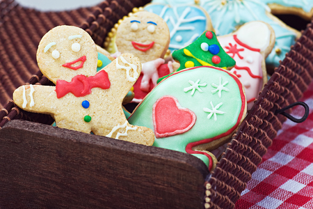 smiling gingerbread man cookies and the rest in a gift box. Focus on the first cookie photo