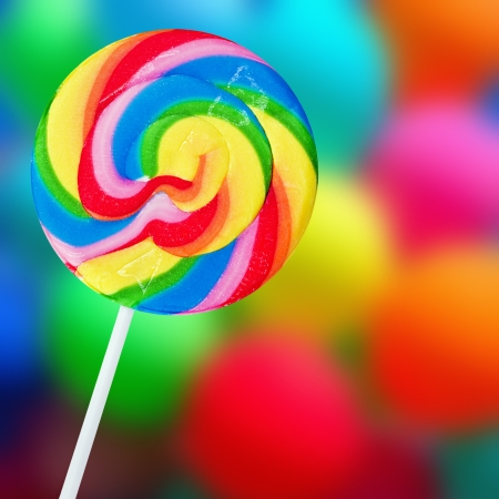 Colorful spiral lollipop on a colored background