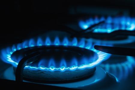 Blauwe vlammen van gas branden van een keuken gasfornuis Focus de voorste rand van de kookplaat Stockfoto
