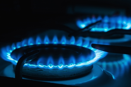 Blue flames of gas burning from a kitchen gas stove  Focus the front edge of the hotplate Stock Photo