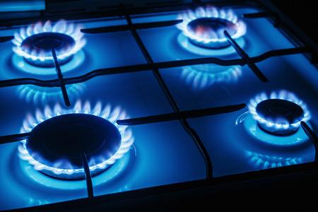 Blauwe vlammen van gas branden uit een keuken gasfornuis. Richten de voorrand van de kookplaat Stockfoto