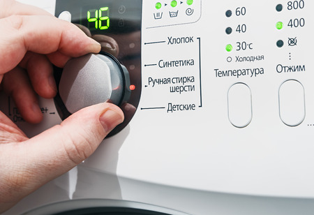Hand selects the washing machine. inscriptions in Russian and focus on the big button photo