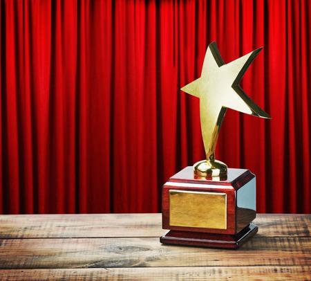 Star award houten tafel en op de achtergrond van rode gordijn Stockfoto