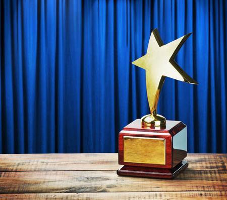 スター賞木製テーブルと青いカーテンの背景に 写真素材