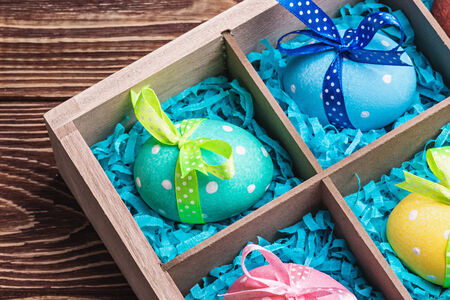 assorted colorful painted easter eggs in a wooden box photo