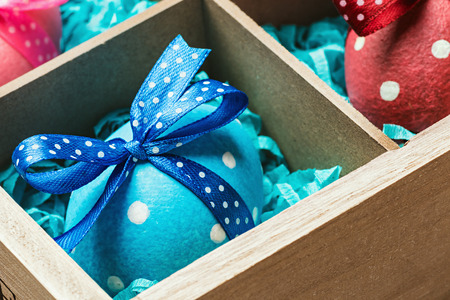 assorted colorful painted easter eggs in a wooden box. assorted colorful painted easter eggs in a wooden box. Focus on blue bows eggs photo