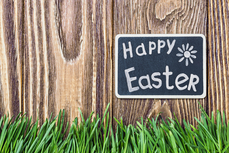 blackboard with the words Happy Easter and green grass on a background of the fence photo