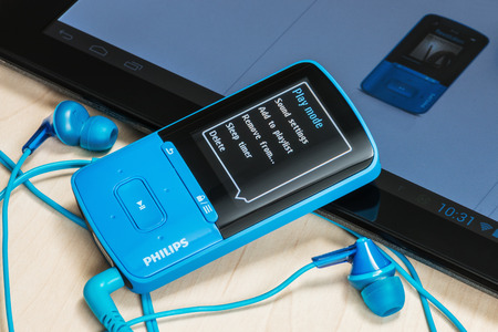 Moscow, Russia - February 27, 2014: MP4 Media Player included with Philips headphones on the table. Concern Phillips was founded in 1891. Its founders are brothers engineers Gerard and Anton Philips.