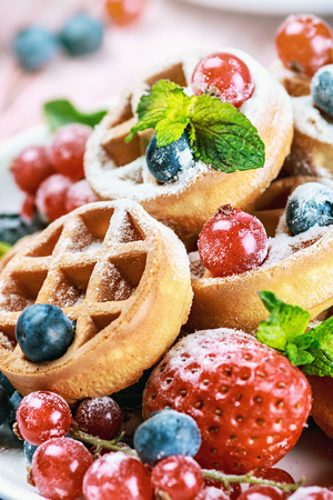 Waffles with fresh berries on the table. Focus on a red currant in the middle frame. small depth of field photo
