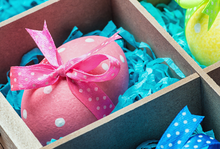 colorful painted easter eggs in a wooden box photo