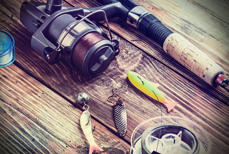 fishing tackle on a wooden table. toned image photo